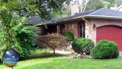Accentuated Window Trimmings, Doors, Deck, & Fence For This Charming Pelham Home